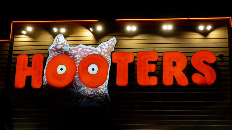 Outside a Hooters restaurant with logo and sign
