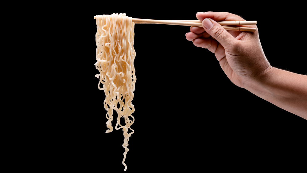 Holding ramen noodles on chopsticks