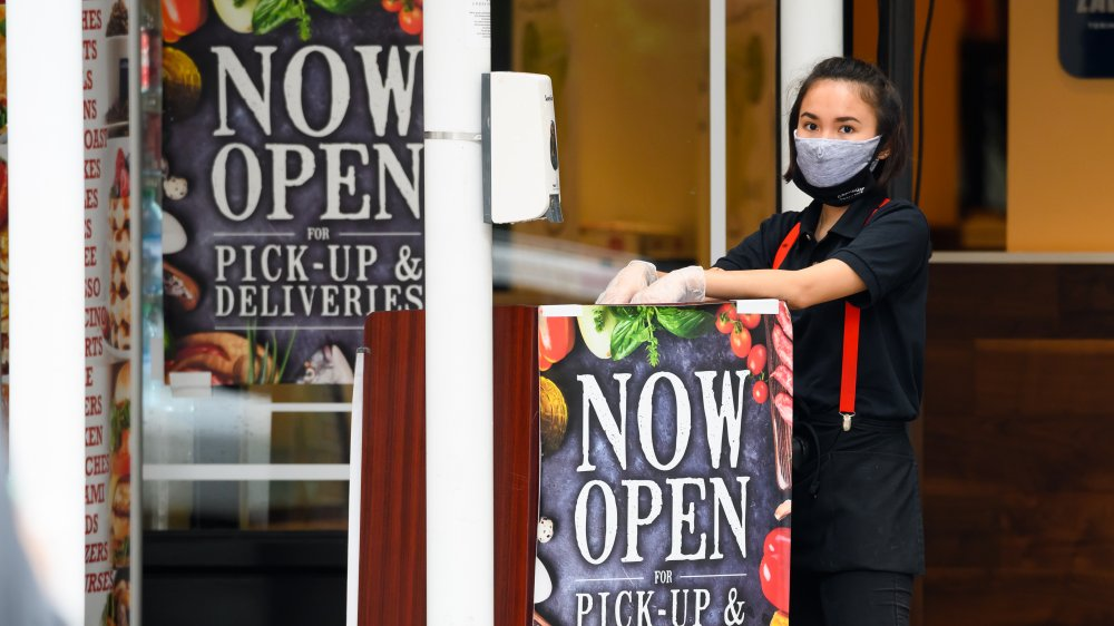 Female restaurant employee with face mask by open sign