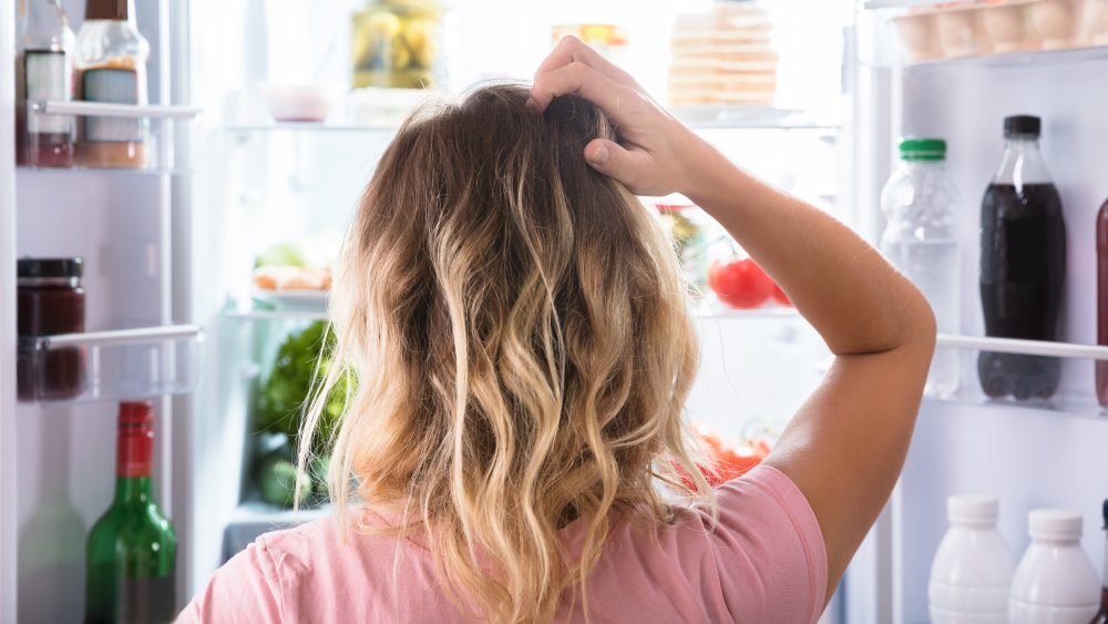 woman looking confused in front of refrigerator