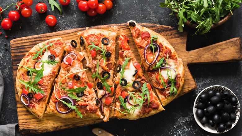 Top view of vegetable pizza on wooden board next to olives