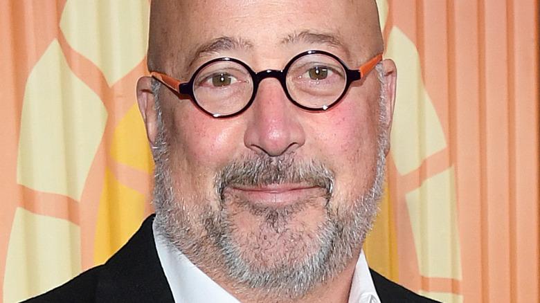 Andrew Zimmern wearing glasses against orange background