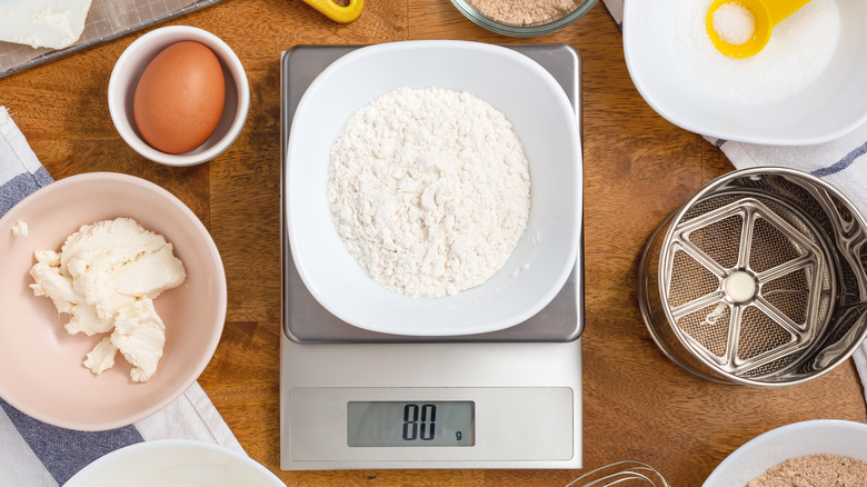 Flour on a digital kitchen scale surrounded by baking ingredients