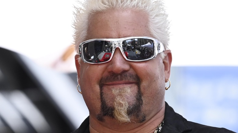 Guy Fieri smiling and wearing sunglasses