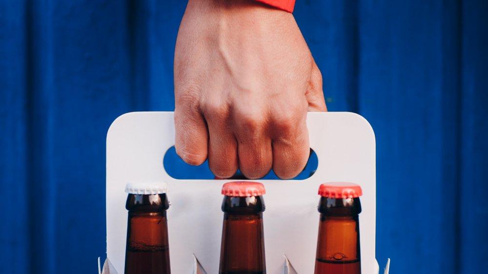 man delivering six pack of beer
