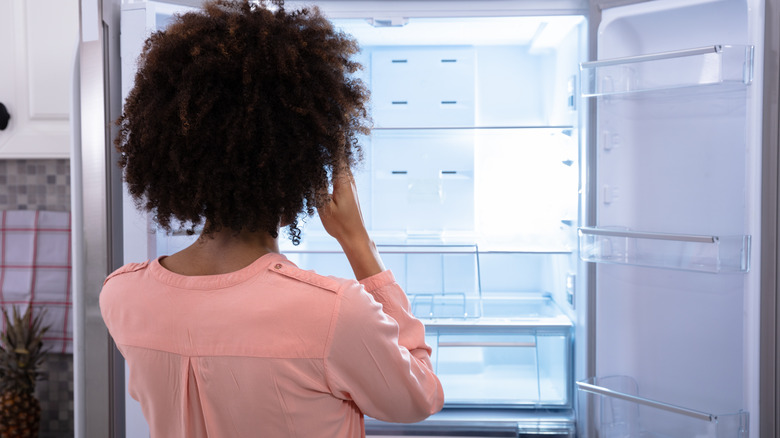 Woman looking into empty fridge