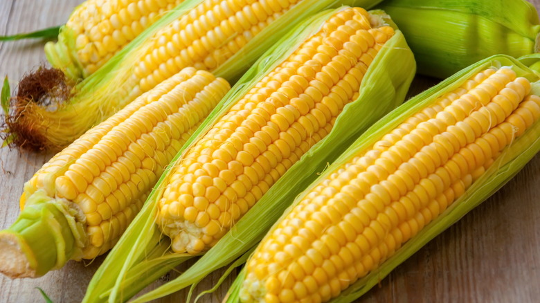 Corn on the cob on wooden surface