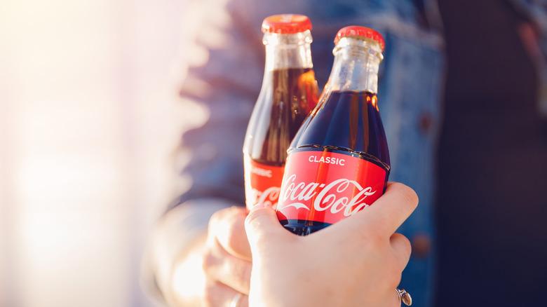 Hands clinking Coke bottles