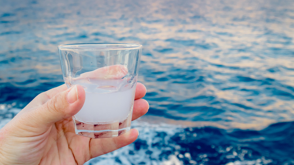 hand holding ouzo in a glass
