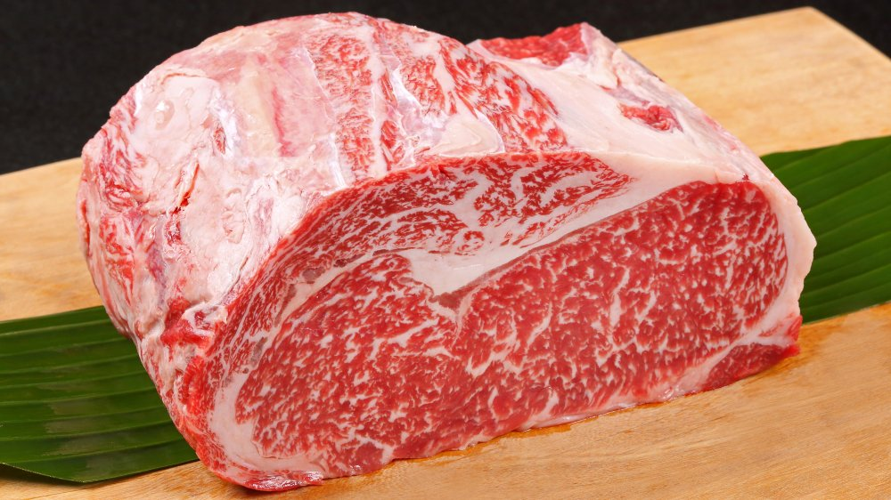 A cut of wagyu beef on a wooden board