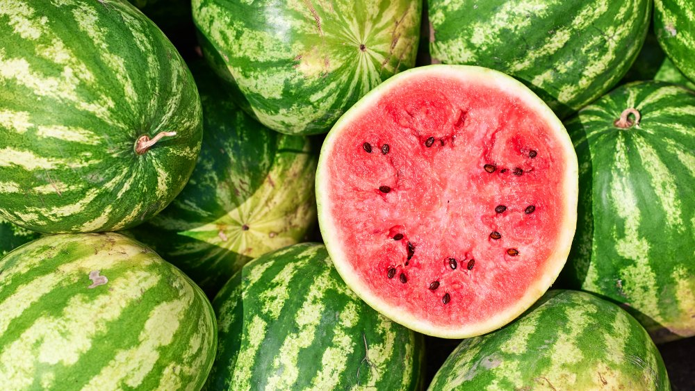 Cut ripe watermelon on top of whole watermelons