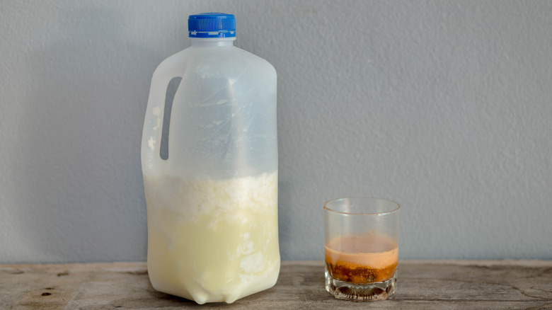 expired milk in a carton next to a glass on a tabletop
