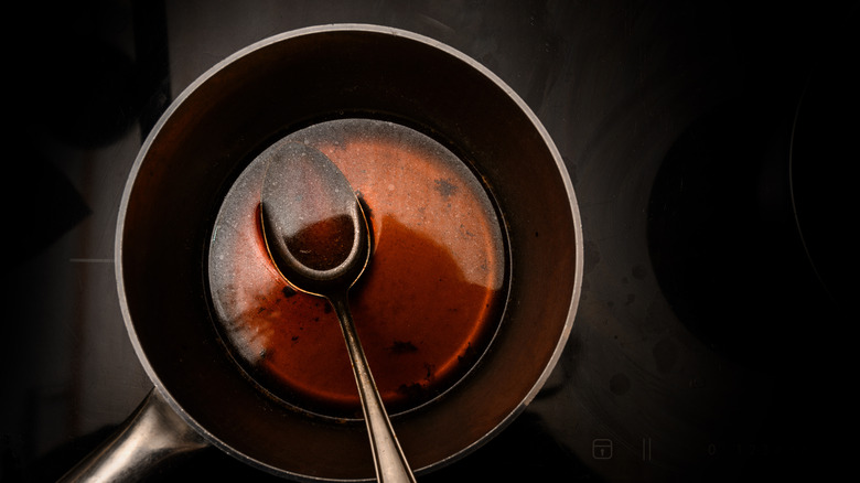Beef stock in pot with metal spoon