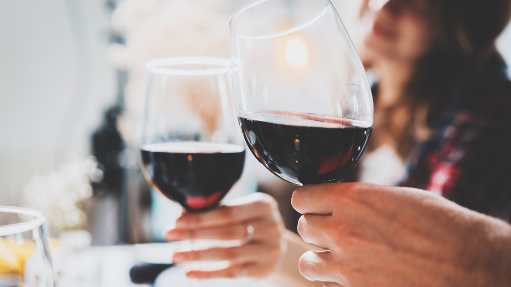 Two people cheers with glasses of wine