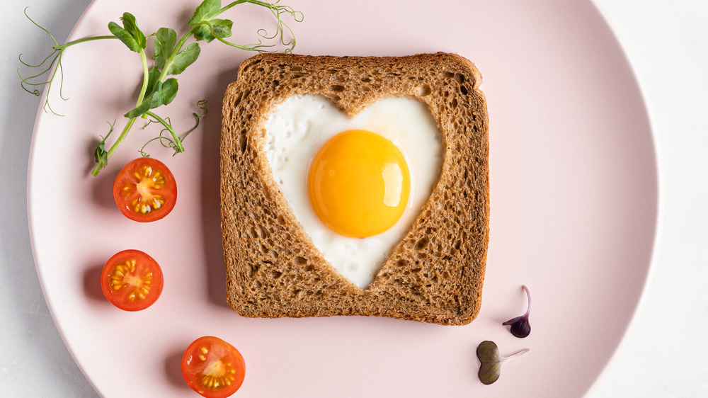Heart-shaped cooked egg on slice of toast