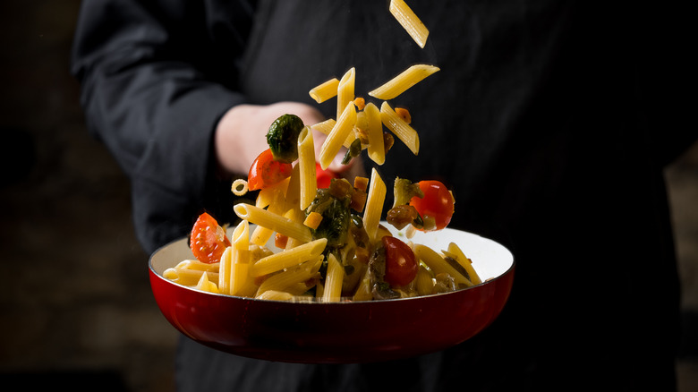 Chef tossing pasta in pan