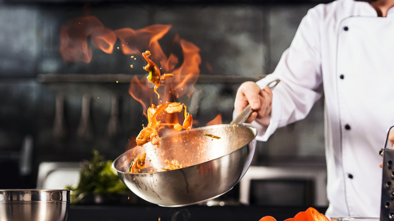 Chef tossing food in flaming wok