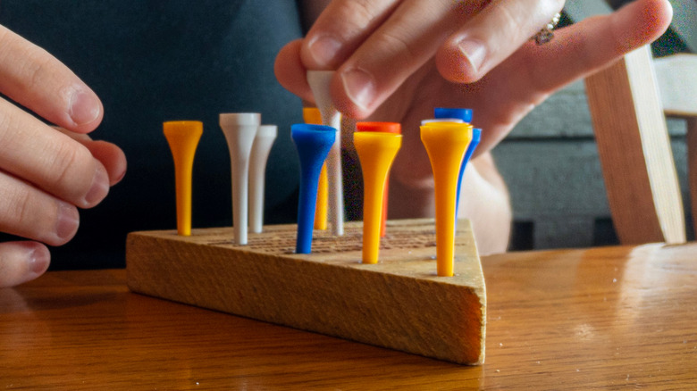 Person playing peg game on wooden table