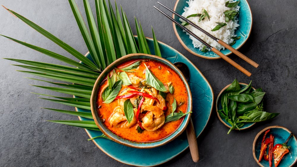 Thai red shrimp curry with a plate of cooked white rice on the side