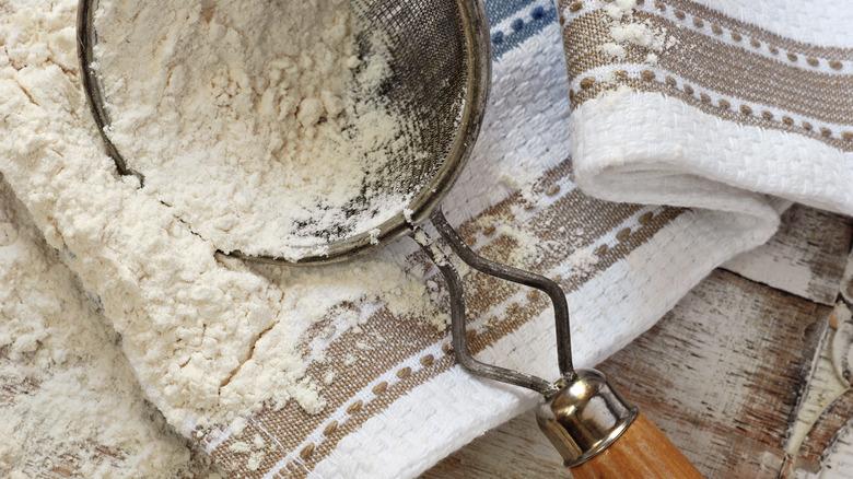 flour and sieve on cloth towel