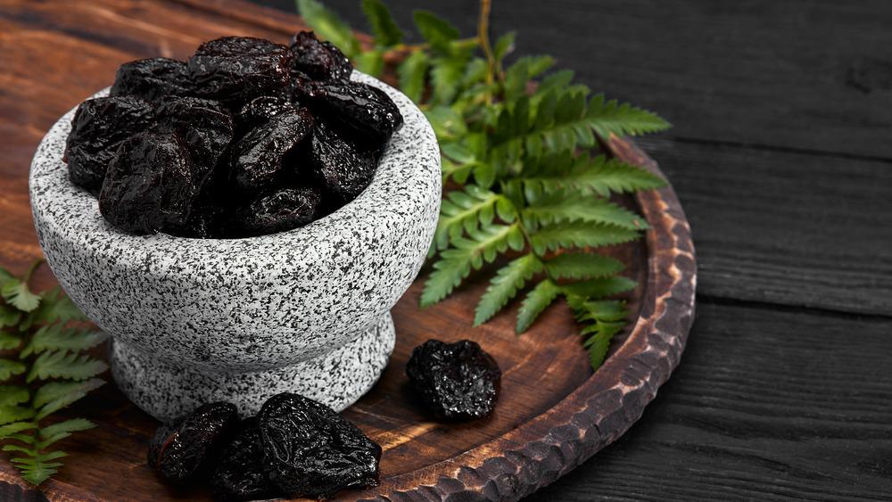 Gray bowl full of prunes on wooden slab