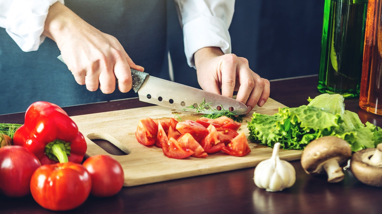 person cutting vegetables with a kitchen knife