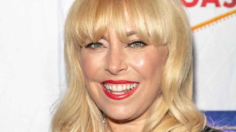 Sutton Stracke smiling in red lipstick
