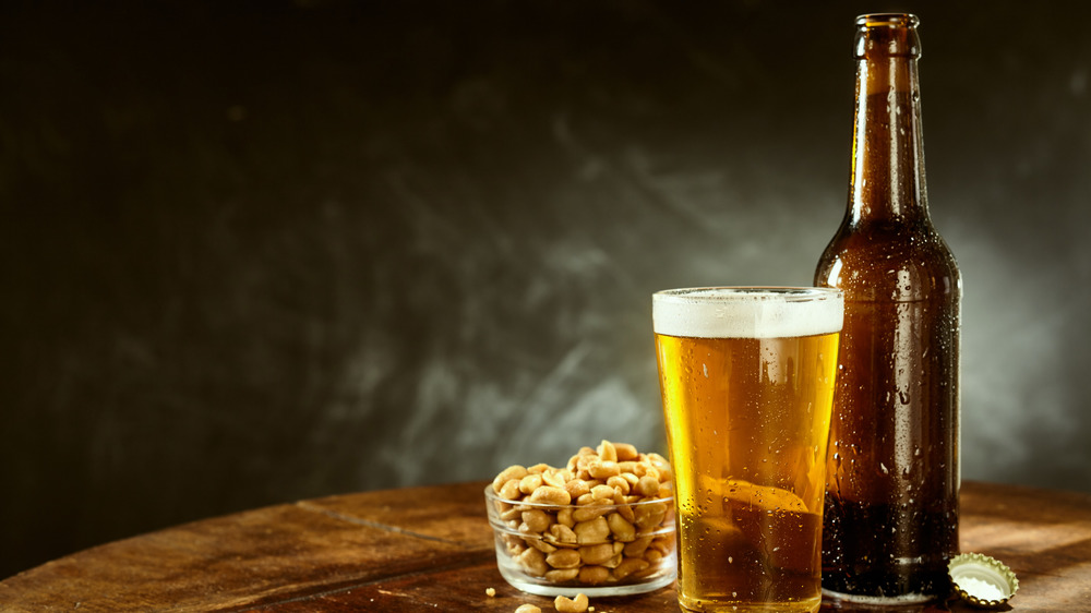 Brown beer bottle, pint glass of beer, glass bowl of nuts and bottle cap on wooden surface