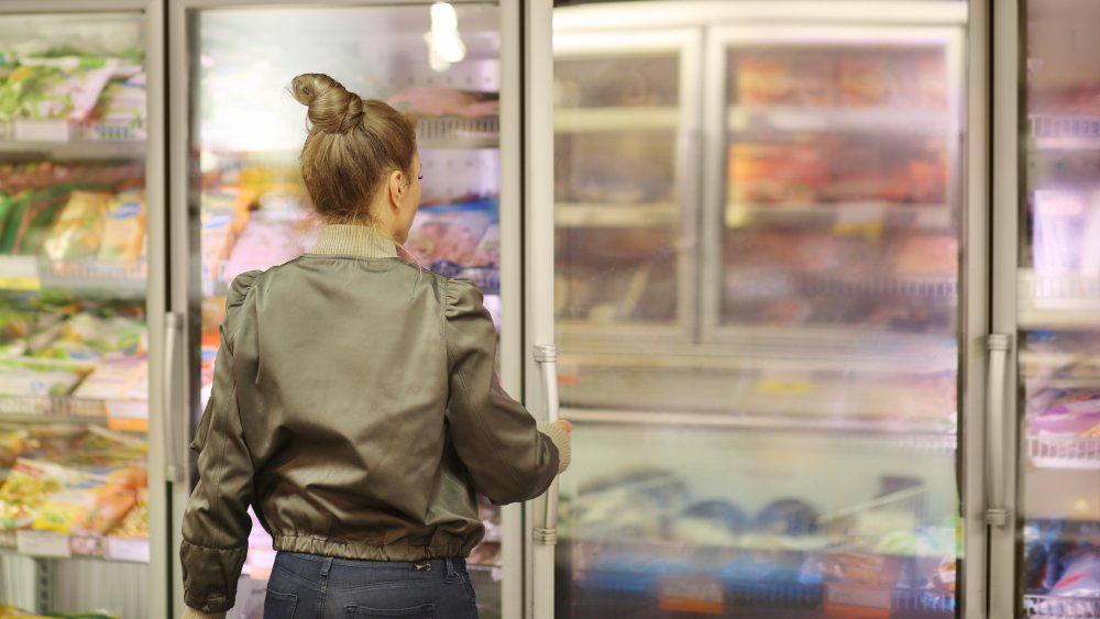 Woman shopping from the frozen food aisle