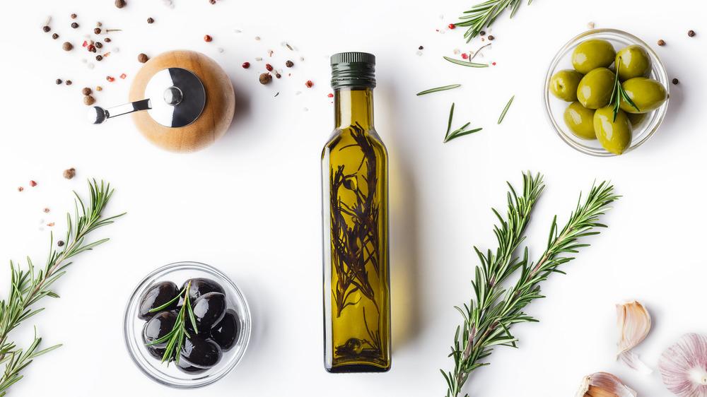Bottle of olive oil next to bowls of olives