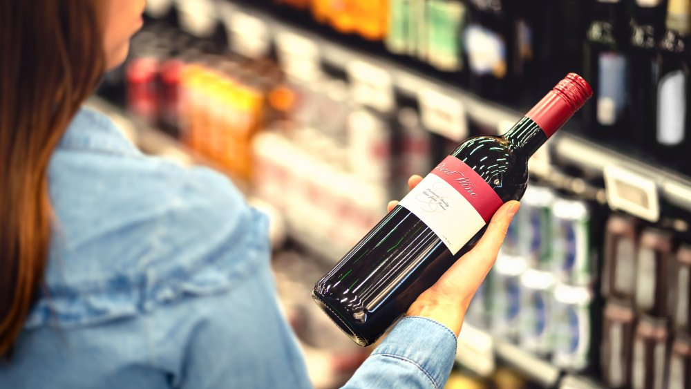 woman holding a bottle of red wine in a grocery store wine aisle