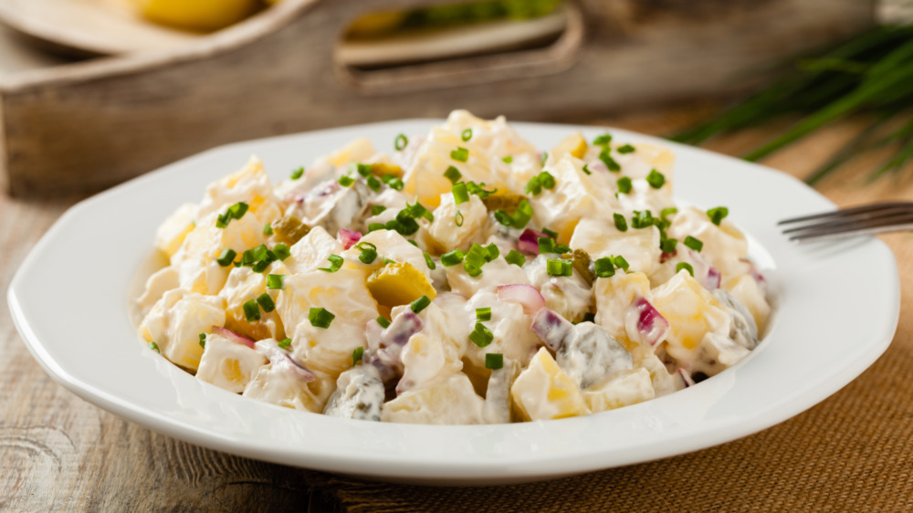 Creamy potato salad with chive garnish