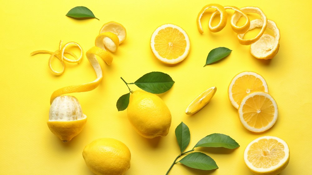 whole and peeled lemons against a yellow background