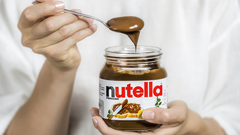 Person holding jar and spoonful of Nutella