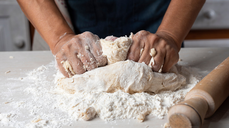 Hands kneading flour on a table