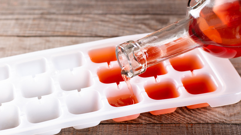 wine being poured into ice cube tray