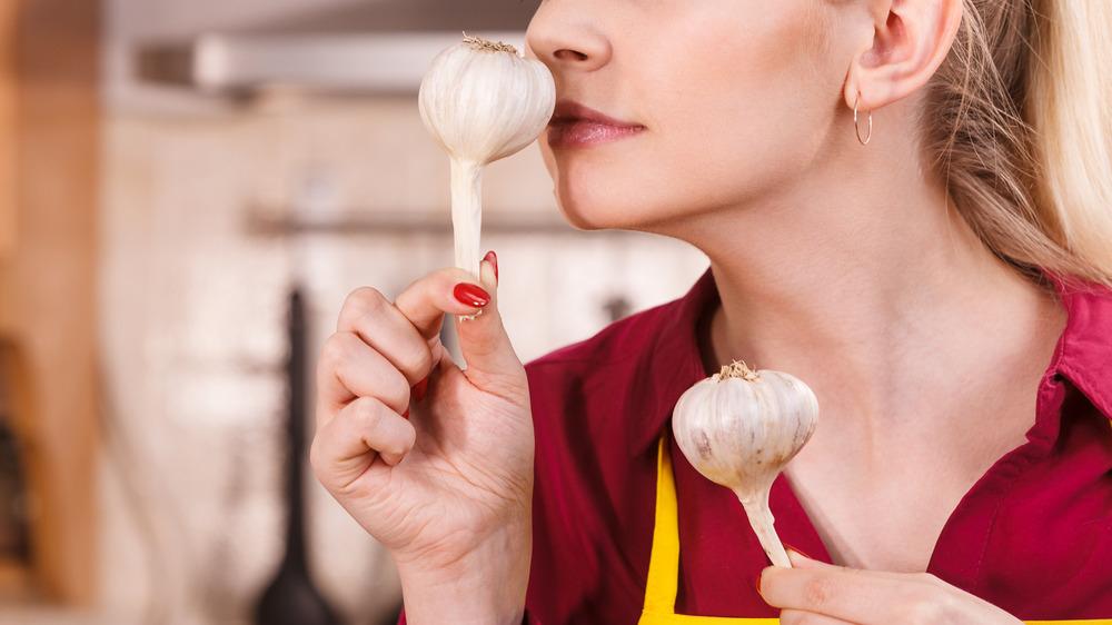 Woman smelling a head of garlic