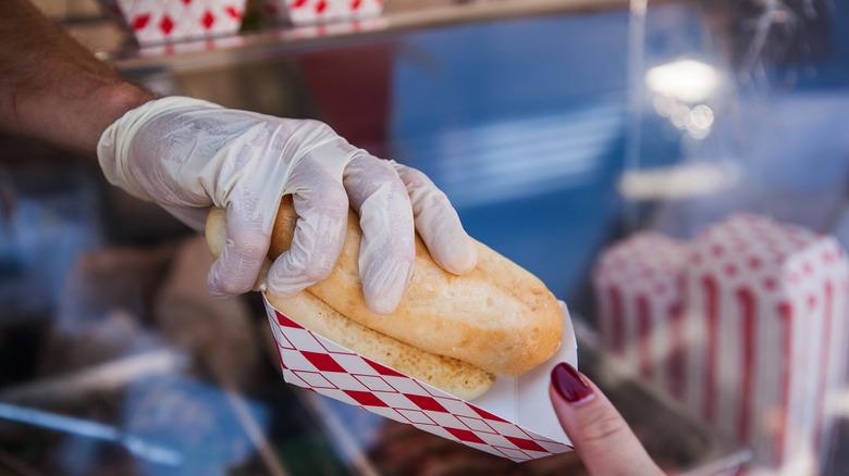 vendor passing hot dog to customer