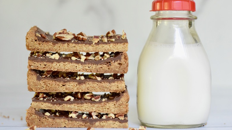 stacked homemade toffee bars with a jar of milk