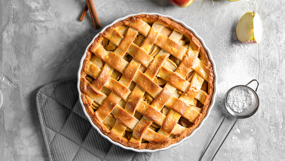 traditional apple pie with lattice crust on plain background