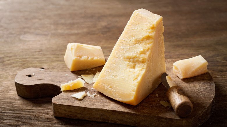 Wedge of Parmesan cheese on wooden board