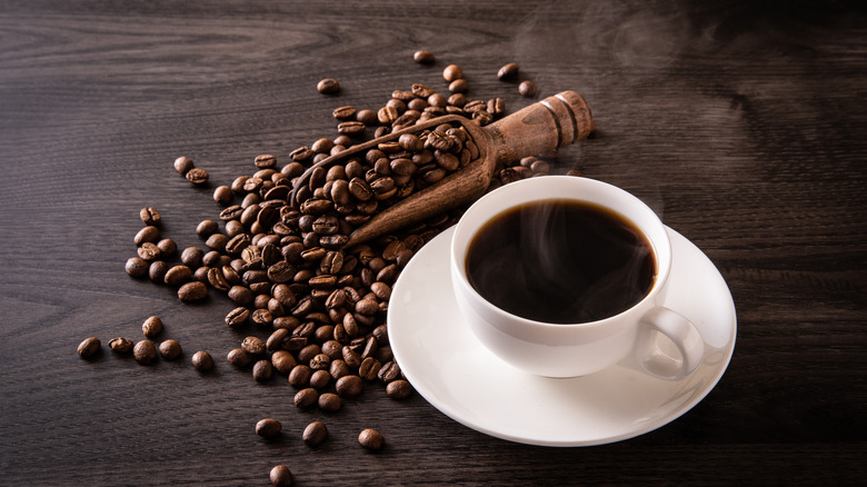 Hot coffee with beans on table