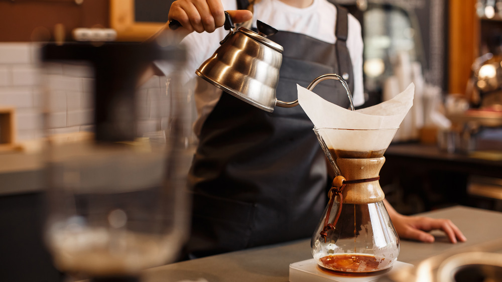 Person pouring water over a coffee