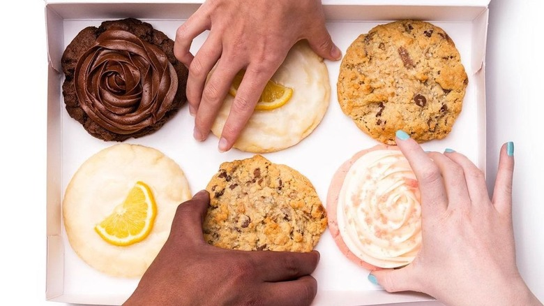Hands reaching for Crumbl Cookies
