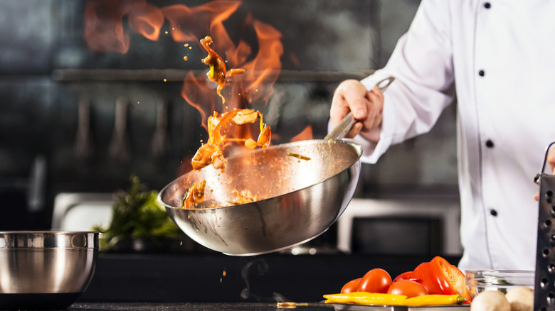 Chef tossing ingredients in flaming pan