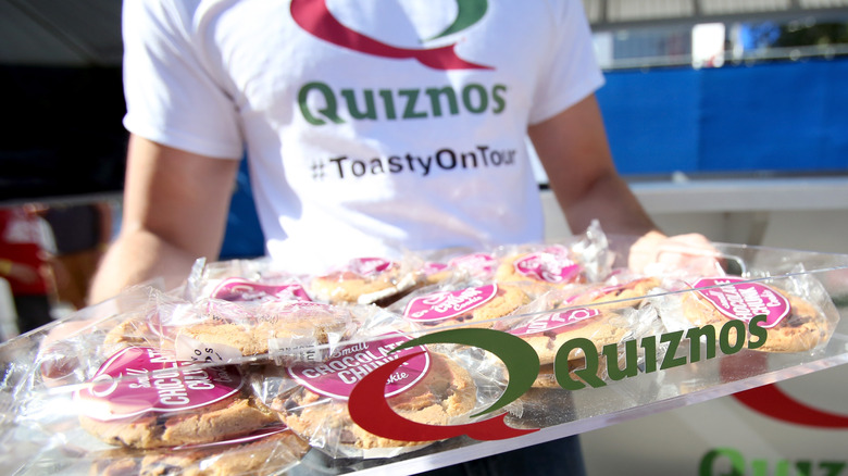 Quiznos employee carrying cookie tray