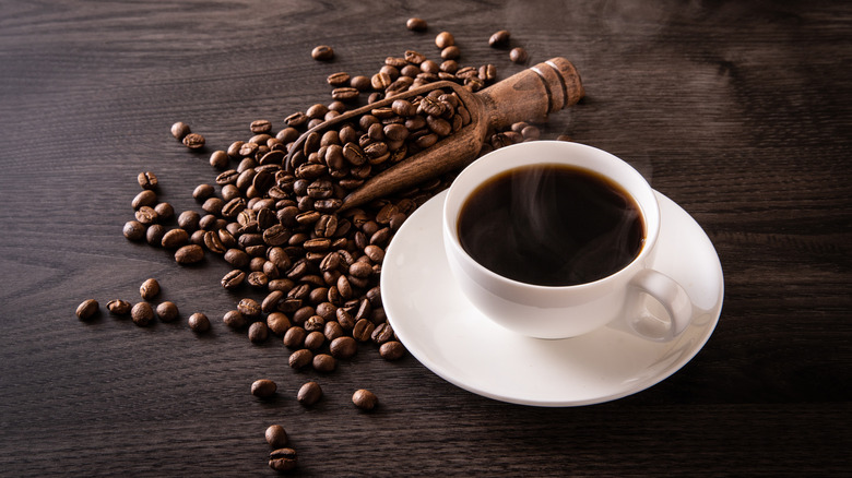 Cup of black coffee and coffee beans on table