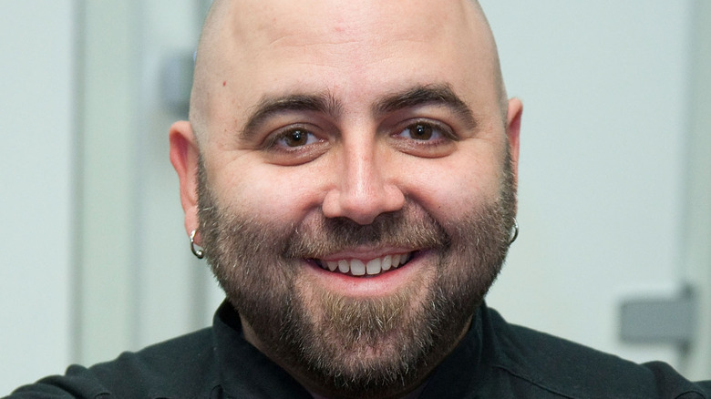 Duff Goldman smiles with earrings and a beard