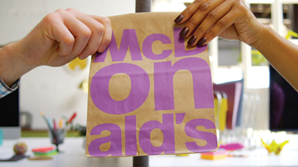 Two people hold McDonald's bag