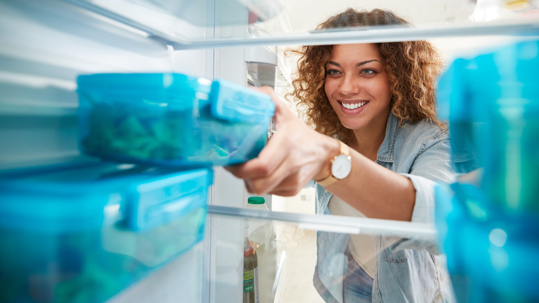 Woman pulling container from refrigerator
